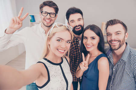 Group of happy smiling businesspeople making selfie and gesturing Stock Photo