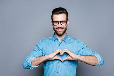 Portrait of happy handsome man in glasses making heart with fingers 版權商用圖片