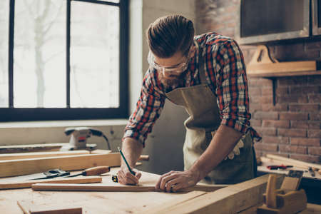 Bearded handsome cabinetmaker at the tabletop with pencil drawing sign on plank.  Stylish craftsman with brutal hairstyle and saved glasses work at his workstation