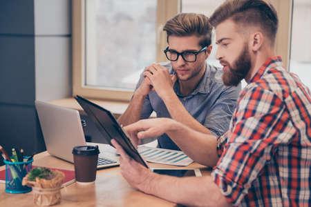 Team van twee zakenmannen bespreken nieuw project met behulp van tablet in het kantoor
