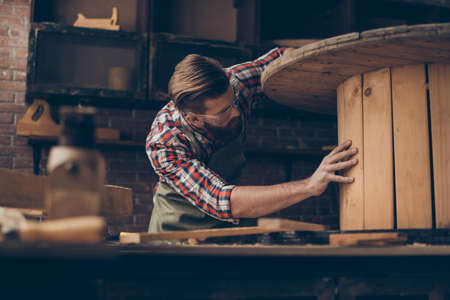 handsome joiner check wood.  Stylish young entrepreneur with beautyful hairstyle and saved glasses work at his workstation. he love his job and workplace