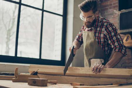 jonge stijlvolle meubelmaker met bril en kapsel. De sterke knappe zaag van de vakmanholding en houten spatie op het werk