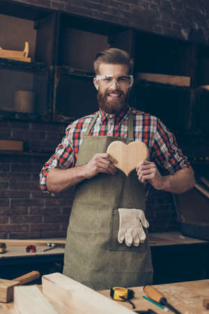Happy handsome joiner in love holding and showing wooden heart near tabletop with tools.  Stylish young entrepreneur with beautyful hairstyle and saved glasses smile at his workstation. He love his job