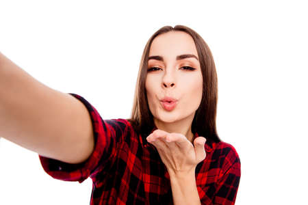 Pretty happy young woman making selfie and sending air kiss Stock Photo