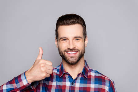 Young handsome man smiling and gesturing thumbs up sign against gray background Фото со стока