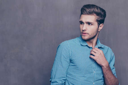 Thoughtful stylish man standing in front of gray background and touching his collar Stock Photo