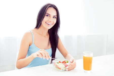 A cheerful young woman eating fresh organic salad and drinking orange juice for breakfast Stock Photo