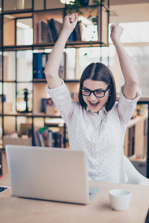 triumphing: Happy glad female manager triumphing with raised hands Stock Photo