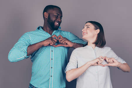 afroamerican: Two happy multiethic lovers making hearts with fingers