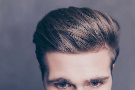 Close up photo of a young mans hair on gray background