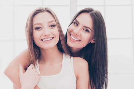 pijamada: Portrait of two beautiful cheerful girls with beaming smiles huging