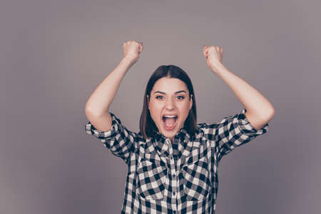 triumphing: Excited young woman triumphing with raised hands isolated on gray background