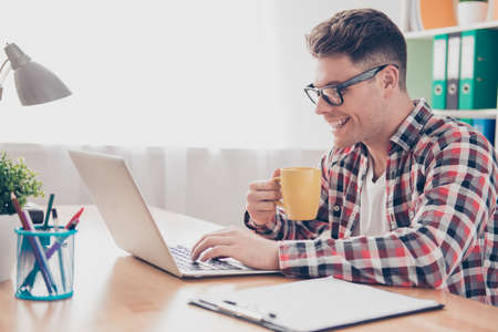 Happy smiling man drinking tea and working with laptop
