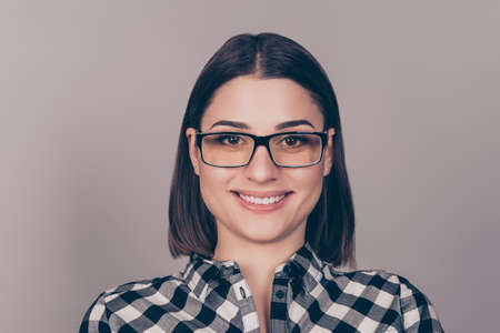 beaming: Young beautiful woman with beaming smile in glasses and checkered shit looking at camera Stock Photo