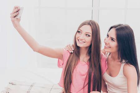 pijamada: Happy beautiful best girlfriends making selfie onj smartphone