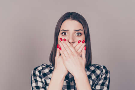 Close up of pretty young surprised woman covering mouth with her hands standing against gray background