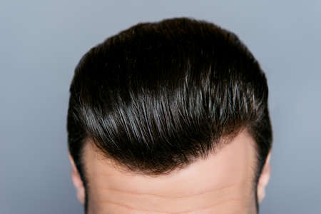 A close up of a mans stylish hairdo without dander isolated on gray background