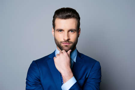 青いスーツとネクタイのあごと考えに触れることで深刻なファッショナブルなハンサムな男の肖像