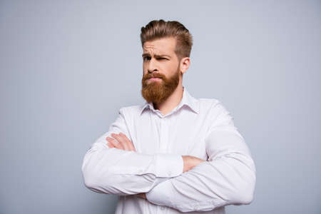 Portrait of serious confident bearded man keeping  crossed hands and expressing distrust emotion