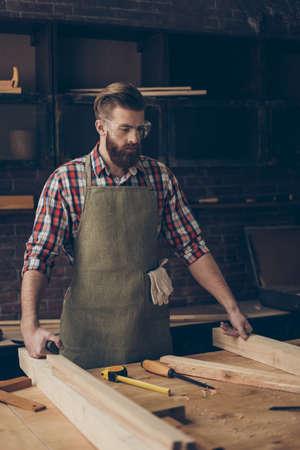 Jonge geconcentreerde modieuze houtbewerker met veiligheidsbril bij het tafelblad die houten meubilair in timmerwerk maken