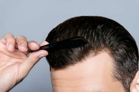 wayout: A close up of a mans hand combing hair without dander Stock Photo