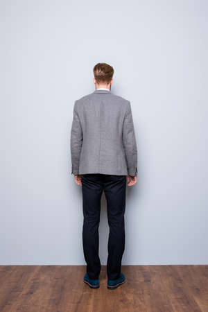 Full-length back view portrait of smart  confident  bearded man in formalwear