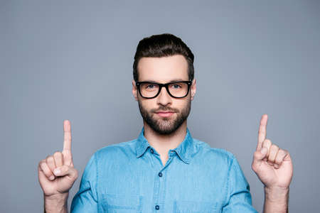 Portrait of happy fashionable handsome man in jeans shirt and glasses pointing up with fingers