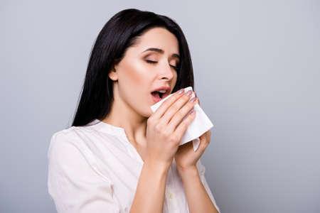 Horizontal portrait of young sick woman sneezing in napkin Stock Photo