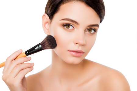 Sensual young woman on isolated white applying blusher on her cheekbones using make-up brush Stock Photo