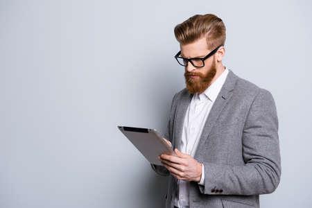 Portret van ernstige zelfverzekerde bebaarde man in formalwear bedrijf digitale tablet en werk