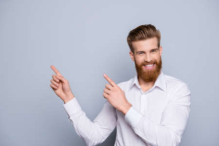Portrait of serious confident bearded man pointing with fingers on copy space and smile