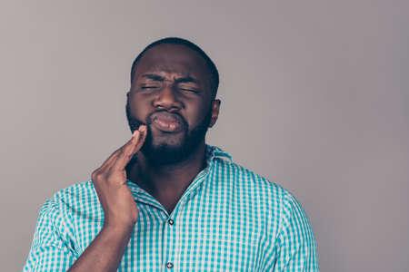 Afroamerican のひげを生やした男の肖像画は、頬をタッチします。彼強い歯が痛い