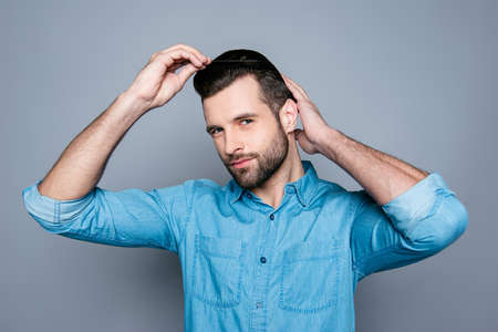 comb: A portrait of a handsome confident man in jeans shirt combing his hair Stock Photo