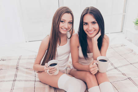 uppers: Young happy smiling women sitting on the bed and drinking hot coffee Stock Photo