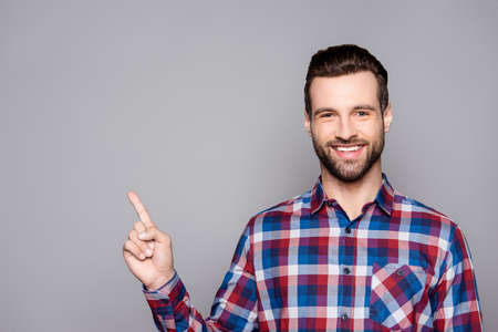 beaming: A portrait of a young happy smiling man in checkered shirt isolated on gray background poiting on copyspace Stock Photo