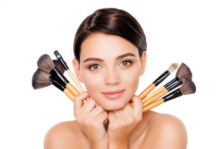 Attractive cute smiling girl holding make-up brushes