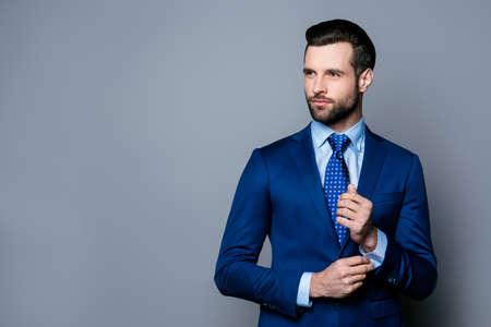 Portret van ernstige modieuze knappe man in blauwe pak en stropdas manchetknopen dichtknopen