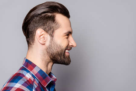 A side view portrait of young handsome smiling man with stylish haircut standing against gray background