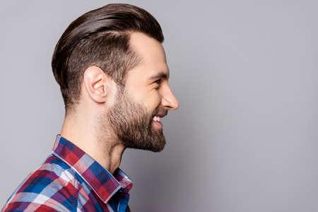 Een zijaanzichtportret van de jonge knappe glimlachende mens met modieus kapsel die zich tegen grijze achtergrond bevinden Stockfoto
