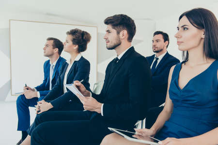 couching: Portrait of confident young managers on financial business seminar
