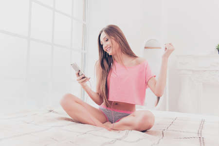 An image of charming young smiling girl sitting on the bed, holding her smartphone and listenint to music
