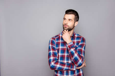 A portrait of young lost in thought freelancer touching his chin and looking up against  gray background