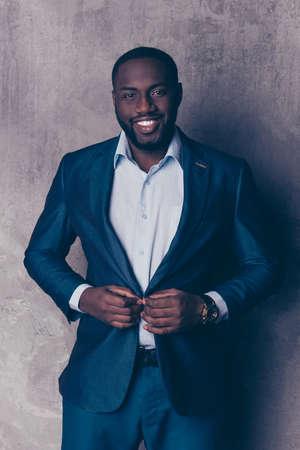 Het portret van de knappe gebaarde afro-Amerikaanse mens in formalwear maakt jas vast Stockfoto