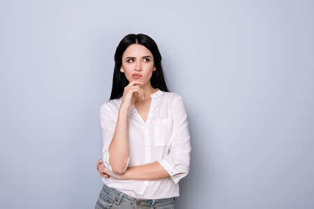 Portrait of beautiful cute young  woman with pouted sensual lips and black hair fink about new idea and looking at something Stock Photo