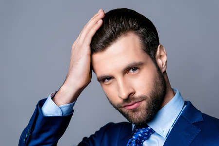 Close up portrait of serious handsome man in blue suit and tie touching his perfect hair