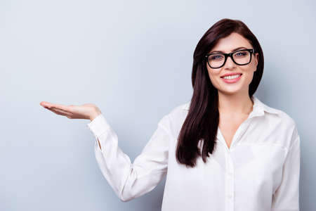 Successful confident young woman presenting new product Stock Photo