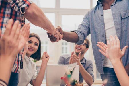 Sluit omhoog van multi-etnische bedrijfsmensen die handen schudden tijdens vergadering