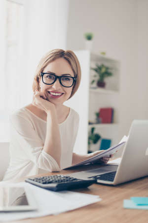 Happy cute pretty accountant working with computer and calculator