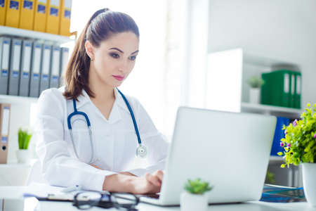 Portrait of serious concentrated doctor sitting at the table and working with computer