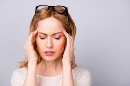 ビジネスの女性は頭痛に苦しんで仕事で疲れてください。